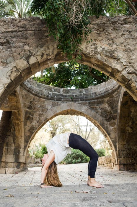 Yoga model in wheel pose in front of an old arch leading into a garden