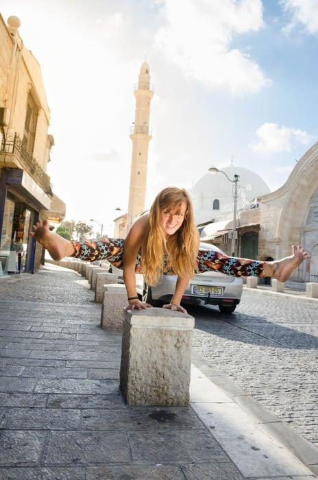 Girl performing a balancing yoga pose on sidewalk guardrail