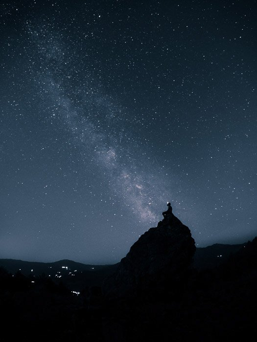 Stunning astrophotography shot of a star filled sky above the silhouette of a man on a rock