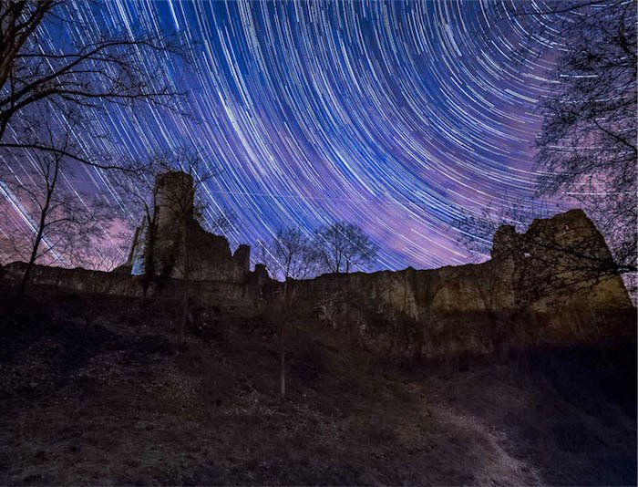 Star trails above a stone building
