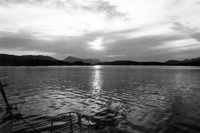 A serene shot of a lake with mountains in the background shot on black and white film