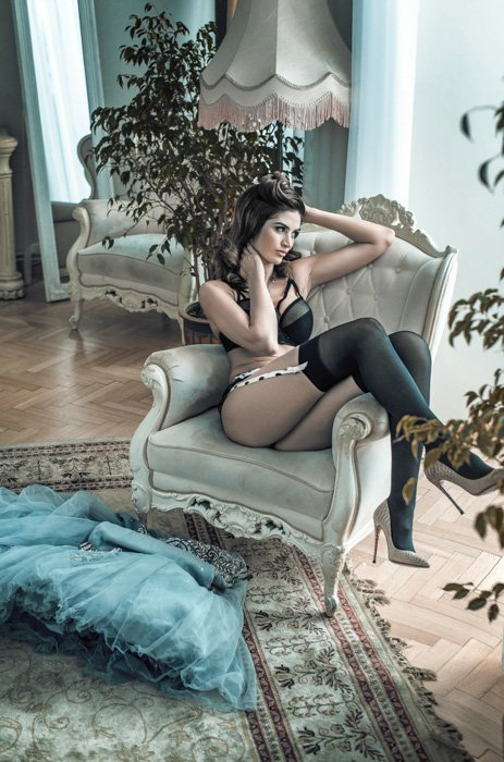 Boudoir photo of a woman sitting on an antique-looking couch