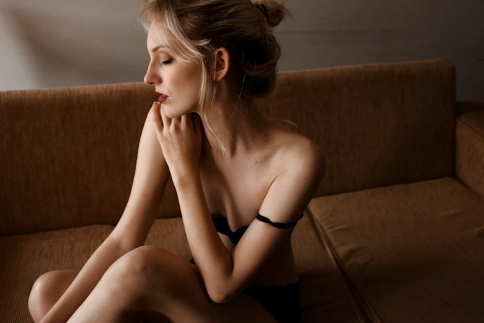 Boudoir photo of a blonde woman sitting on a sofa