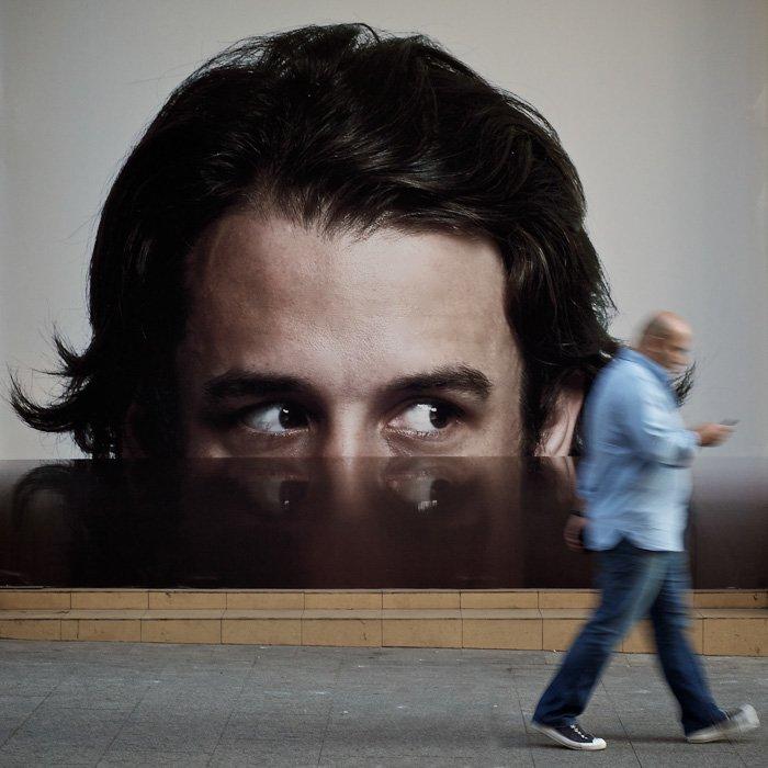 Eyes on an advertisement seems to follow a man walking - street photography