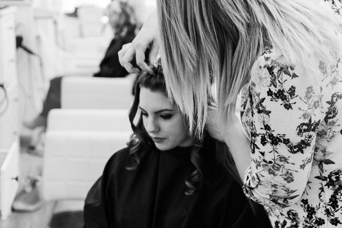 A black and white shot of photography models getting hair and make up done