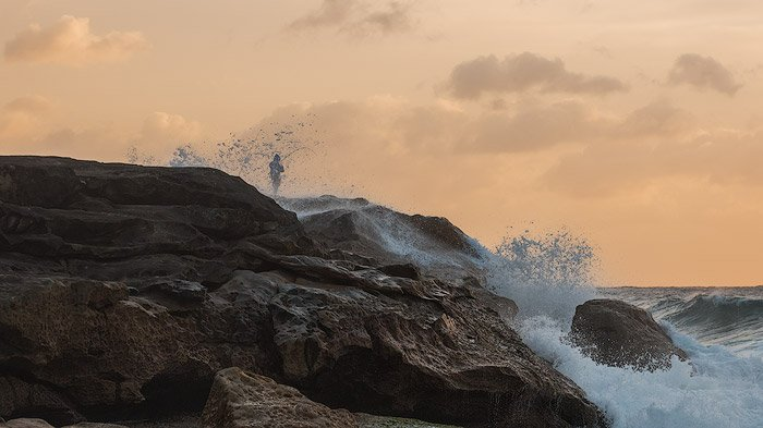 Seascape Photography of a man rocking fishing by the coast