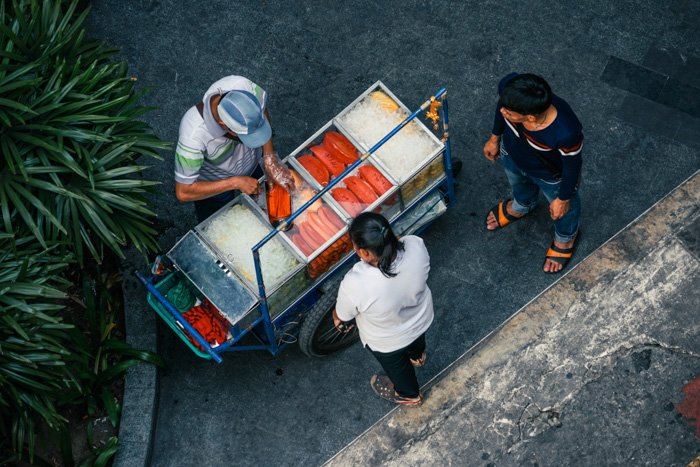 A street photography shot of a food vendor serves food from his cart