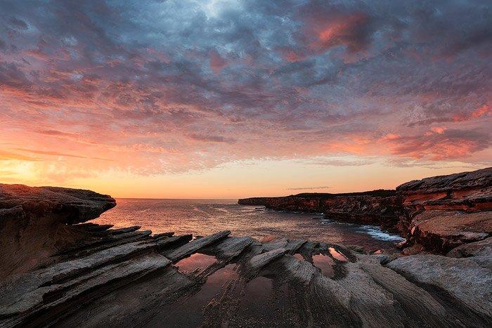 Rock reflections by a coastal seascape at sunrise