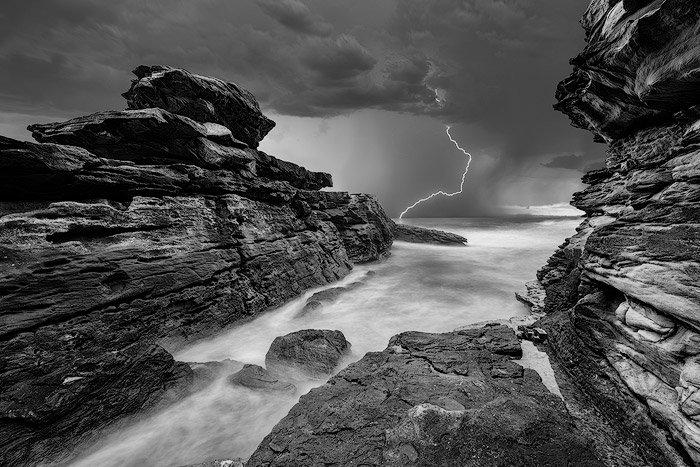 Lightning striking over a rocky seascape