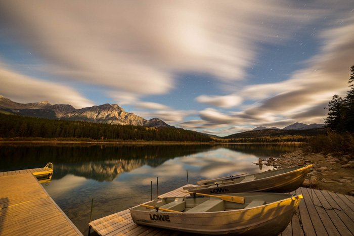 Time lapse photo of boats at a lake