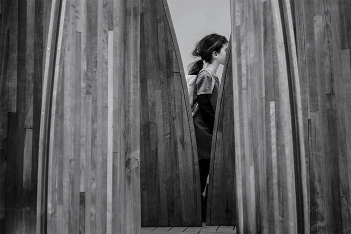 Black and white photo of a young girl walking between some wooden boards