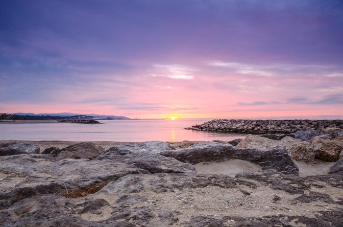 A landscape photo of a seaside at sunset