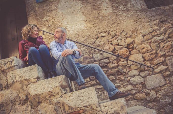 A couple posing on stone steps, looking at each other with amusement