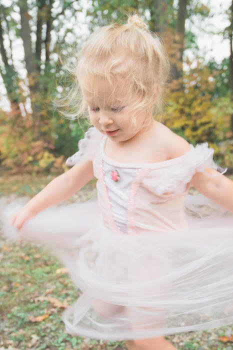 Artistic motion blur photograph of a little girl in a tutu spinning