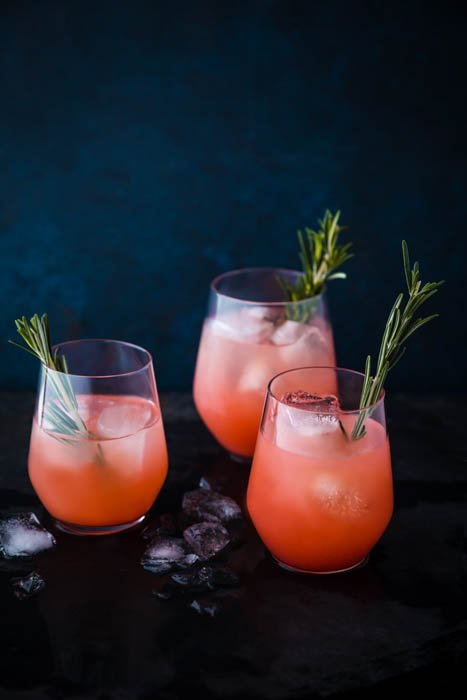 Atmospheric food photography shot of three orange cocktails on rustic background