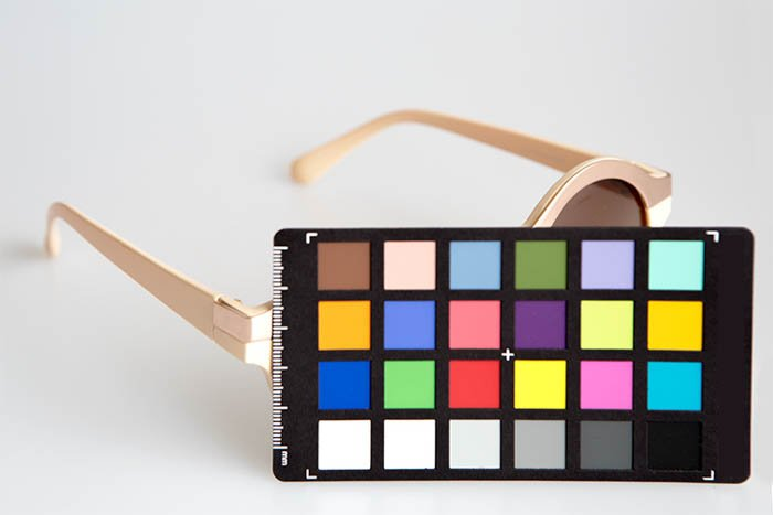 A pair of beige women's sunglasses in front of white background, and a color chart in front on them