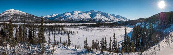 A stunning panoramic photograph of a winter landscape taken in Wiseman, Alaska