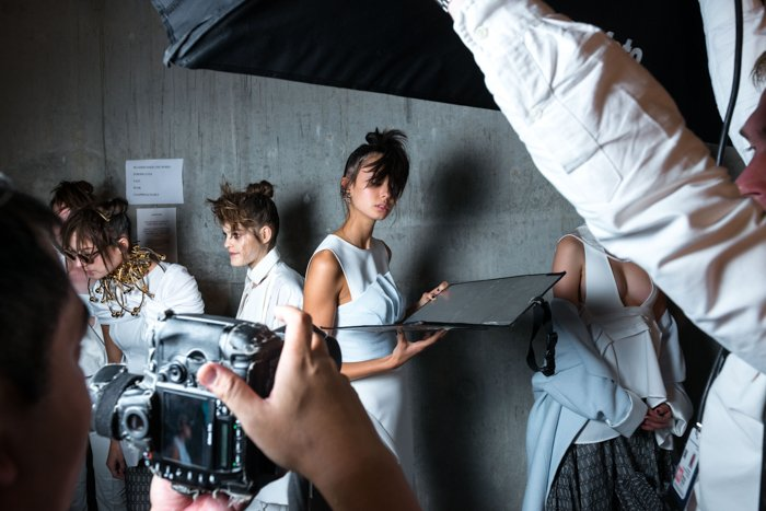 A behind the scenes view of a fashion shoot , using photography reflectors