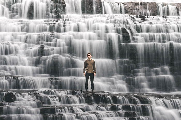 creative self portrait of a man standing in a waterfall