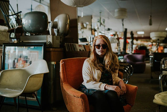 a portrait of a girl sitting in an armchair in a thrift shop