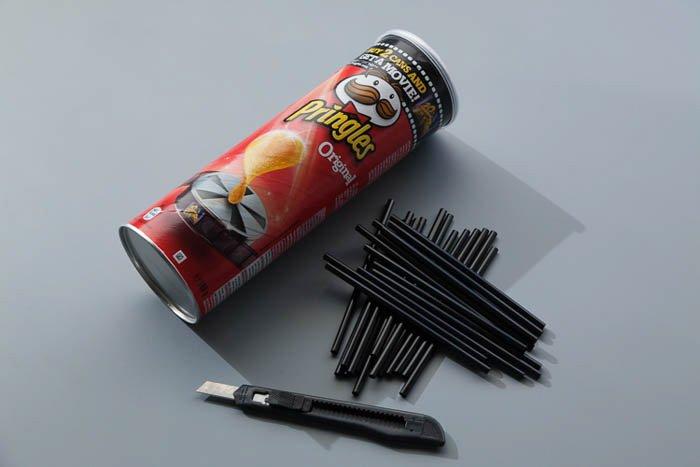 A pringles box, craft knife and straws