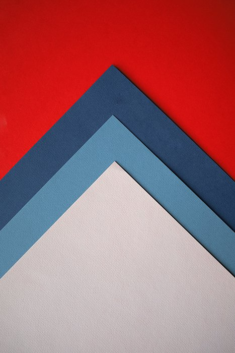 An abstract composition of red, blue and grey colored paper