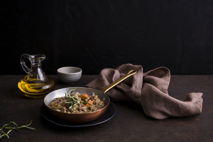 Still life food photography image of lentil soup in a copper pot on table