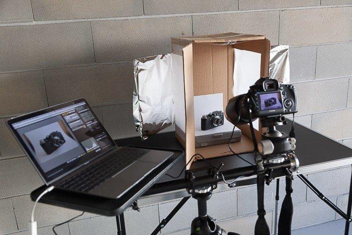 A photoshoot setup containing a laptop, diy light box, dslr camera on tripod