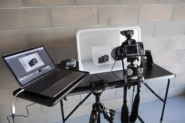 A diy photoshoot setup containing a laptop, diy White Box Flash Diffuser, dslr camera on tripod