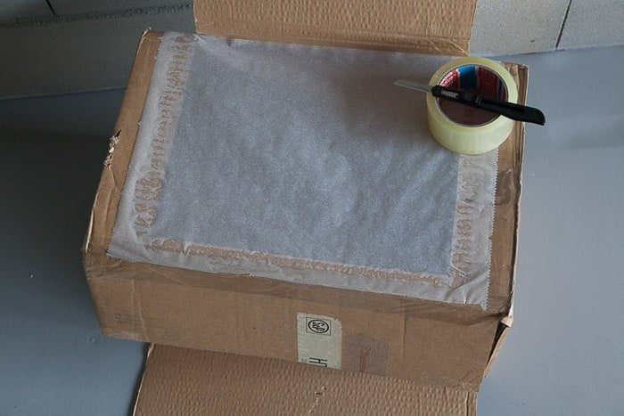 Overhead shot of an open cardboard box and other tools you need to make a light box photography