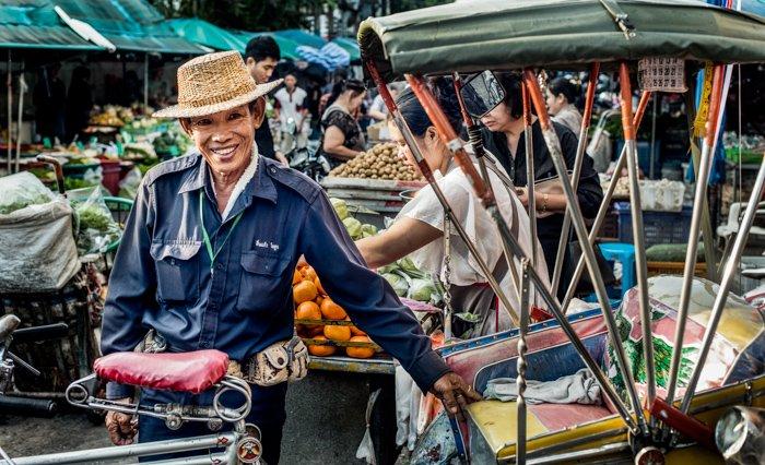 A travel documentary photograph of an Asian man at a street market