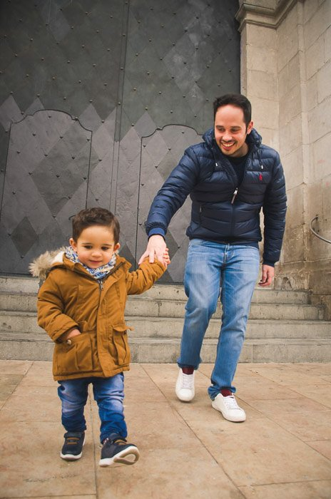 A father and son playfully running towards the camera - family portrait poses