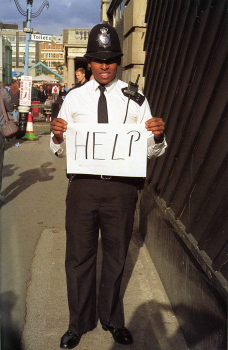 A policeman holding a sign that says help by Gillian Wearing