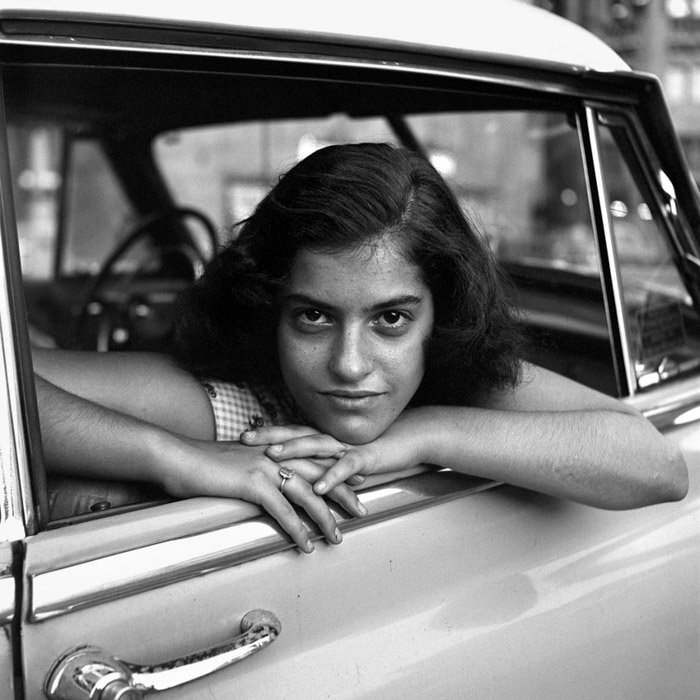 A black and white portrait of a girl in a car by Vivian Maier female photographer