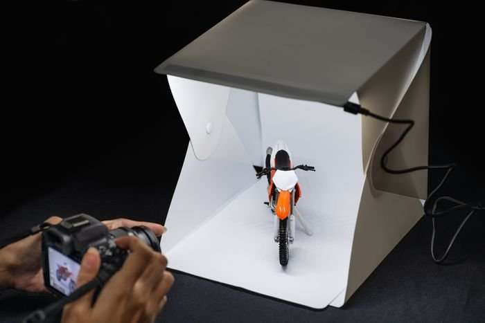 a person photographing a small product in a light box
