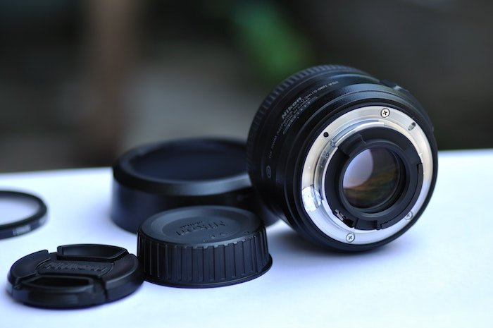 A lens and lens caps laid out on a table