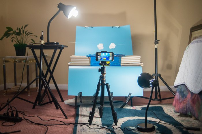A product photography setup with a smartphone on a tripod in front
