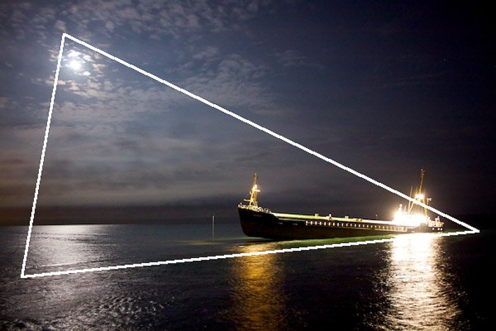 A picture of a ship at sea at night with a composition triangle overlayed - photography composition rules