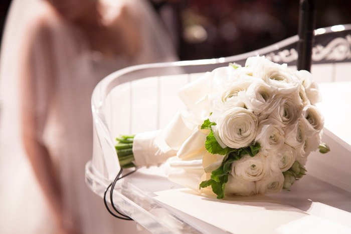 A bridal bouquet with bride sitting in background