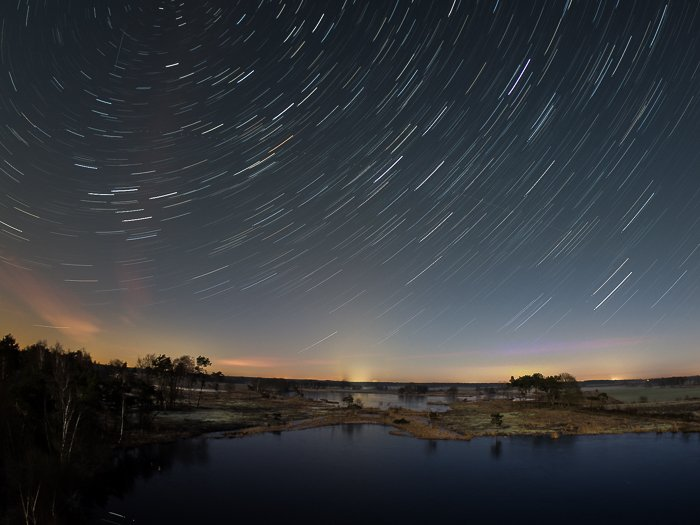 circular star trails above a lake after editing
