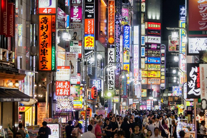 A street photography image with neon hoardings shot in Tokyo at night