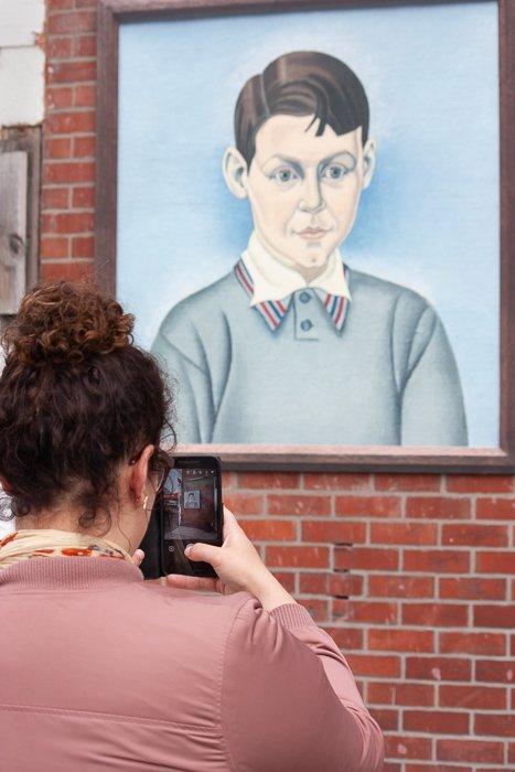Street photography of a women taking photo of street art