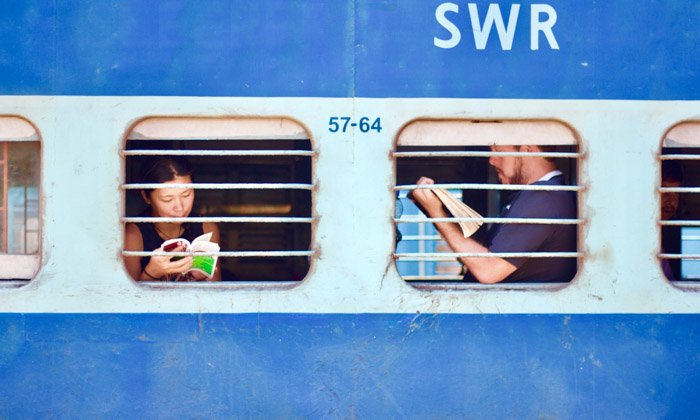 A travel photograph of people reading books on a train