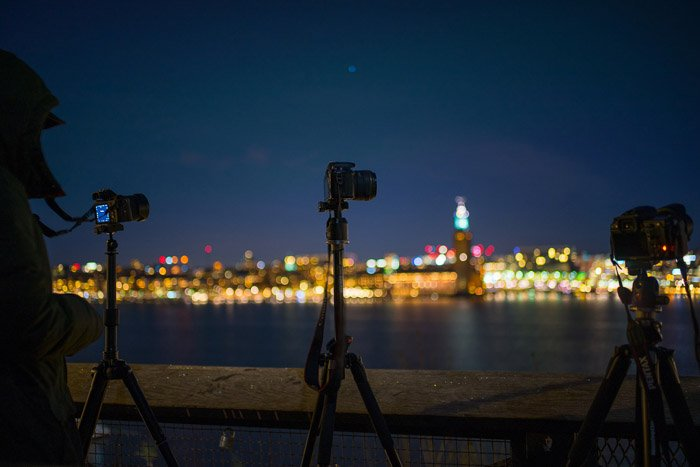 photo of tripods at night on a riverbank