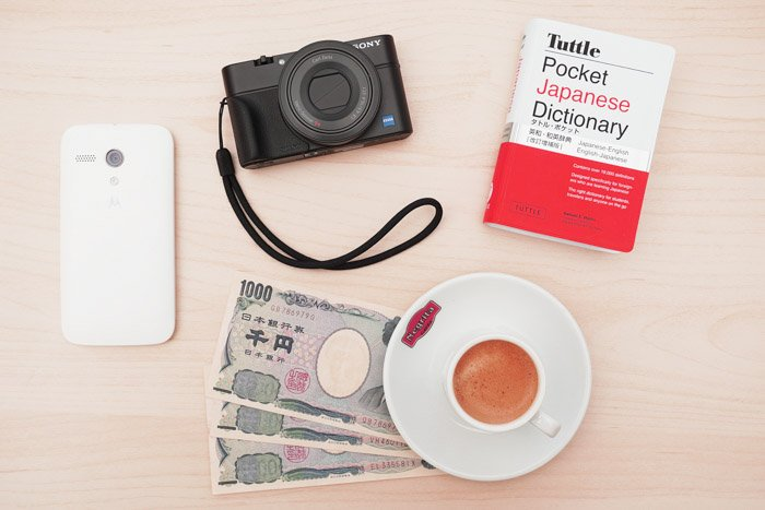 Accessories for travel photography like a guidebook, camera, local money and phone