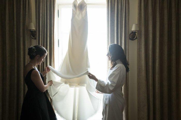 Two women inspecting a wedding dress