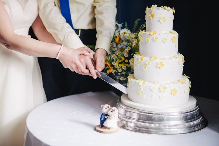 wedding photography of the couple cutting a cake