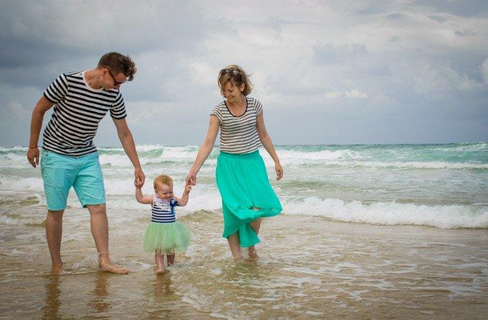 family of three walking through waves on a beach