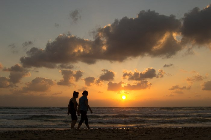 A couple walking on the beach at sunset.
