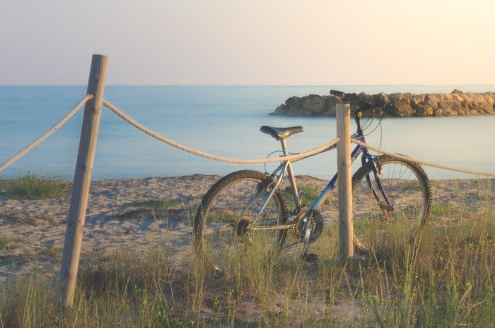 A dreamy photo of a bike resting against a wooden fence with the sea in the background